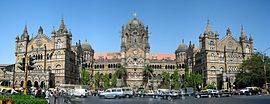 A brown building with clock towers, domes and pyramidal tops. Also a busiest railway station in India.[281] A wide street in front of it