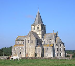 A tall church of grey stone with fine details and a crossing tower topped with a slate-covered spire rises out of rural countryside, where two mares are grazing.