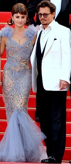 On a staircase with a red carpet stand both a man wearing glasses and a white jacket atop a black business suit, and a woman wearing a blue dress with transparencies.
