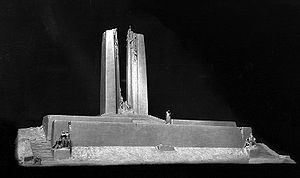 A white plaster design model of the Vimy Memorial from the front side, displayed against a black background.