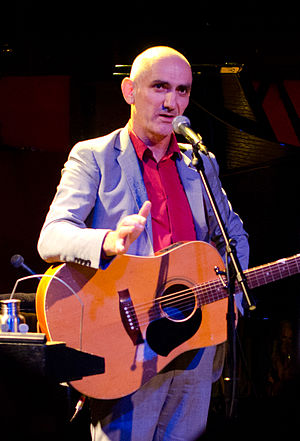 56-year-old Kelly is standing at a microphone with his guitar slung over his shoulders. His right arm is bent at the elbow towards the viewer, while his left is at his hip. He wears a grey suit with an orange shirt.