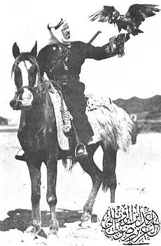 A black-and-white photograph of a mounted man on a dark horse. A hawk is perched on the man's outstretched hand.