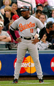 "A man with dark skin stands on a baseball diamond. He is wearing a gray baseball uniform, which reads ""Orioles"" across the chest, and a black baseball helmet with a bird. He stands with arms akimbo and looks to the left of the image."