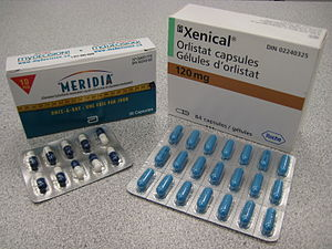 The cardboard packaging of two medications used to treat obesity. Orlistat is shown understanding under the brand name Xenical in a white package with the Roche logo in the bottom right corner ( the Roche name within a hexagon). Sibutramine is below under the brand name Meridia. The package is white on the top and blue on the bottom separated by a measuring tape. The A of the Abbott Laboratories logo is on the bottom half of the package.