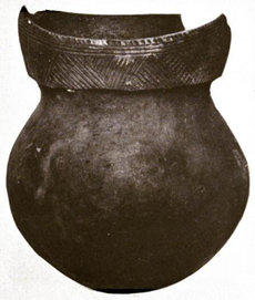 A ceramic pot with a round bottom, short neck and a rim decorated with geometric line patterns. The rim is broken in the rear.