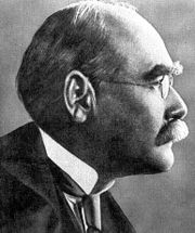 Profile of the balding head of a man in a high collar, tie and coat and with a serious expression. He has bushy eyebrows and a moustache.