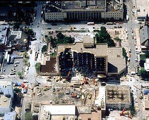 An overhead view shows the Alfred P. Murrah building, half of it destroyed from the bomb's blast. Near the building are various rescue vehicles and cranes. Some damage is visible to nearby buildings.