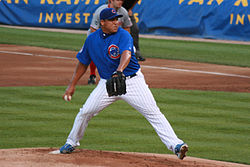 Full shot of pitcher in mid pitch.  Pitcher is wearing a blue hat, a blue shirt with a Cubs logo and white pants