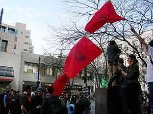 Three red flags with IWW logos being held above a crowd of people.