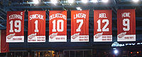 "The banners of six retired numbers. The banners, from left to right, read ""Yzerman 19"" ""Sawchuk 1"" ""Delvecchio 10"" ""Lindsay 7"" ""Abel 12"" ""Howe 9"". The Yzerman banner has a small ""C"" at the top right corner."
