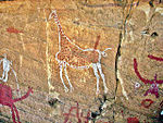 A drawing of a giraffe on a cave wall.
