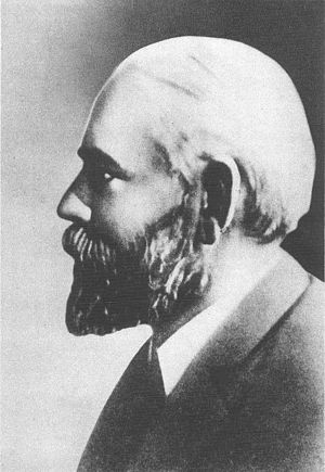 A black-and-white profile photograph of the head and shoulders of a middle-aged bearded man, facing left