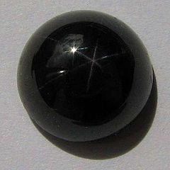 A round cabochon of very dark red garnet which displays a six pointed star effect under intense lighting.