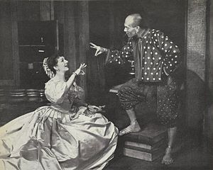 woman kneeling in front of a standing man; the two are conversing and each is gesturing with one hand as if ringing a small bell