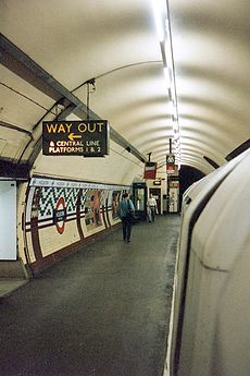 An underground station platform with curved walls and ceiling. A train is alongside the platform.