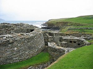 A semi-circular stone wall at left hints at the existence of a large and ancient building and to the right are the ruins of various other stone structures. In the background a low cliff divides a body of water from grassy fields.