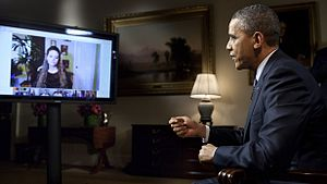 President Barack Obama, seated at right, answers questions about the State of the Union posed by citizens, shown on a flat-screen monitor at left, in the first-ever completely virtual interview from the White House. This interview aired on the official White House Google+ page on January 30, 2012.