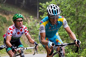 Thomas Voeckler wearing a white jersey with red polka dots, following Fredrik Kessiakoff as they ride up an incline.