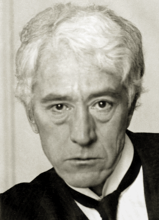 A white-haired man in his fifties, wearing a black jacket and tie and white shirt