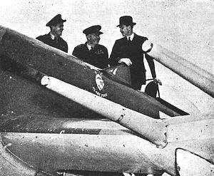 Three men stand next to a fighter aircraft and look at it