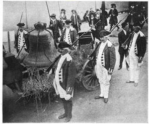 A large bell is seen tied to a wagon. Soldiers in Revolutionary War uniforms stand by.