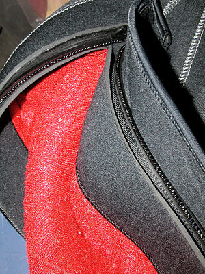 Detail of the zipper of a semi-dry wetsuit, showing one end of an open zipper and the neoprene flaps that cover it on the inside and outside of the suit to protect the zipper, improve comfort, and reduce leakage through the closed zip.