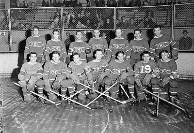 1942 Montreal Canadiens posing for photo on rink. First row of seven players kneeling and second row of seven players standing behind.