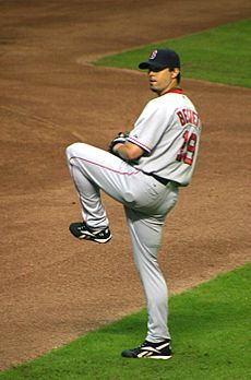 A man in a gray baseball uniform stands on his right foot, ready to deliver a pitch. His right hand is hidden inside of his black baseball glove. The man wears a navy blue baseball cap and has a short goatee.