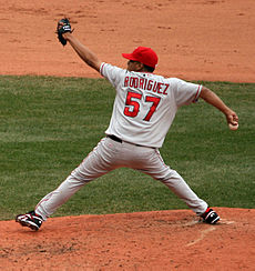 "A man in a gray baseball uniform throws a baseball from a dirt mound. He is wearing a red baseball cap. His back is to the camera, and the reverse of the uniform reads ""Rodriguez"" in red block letters and ""57"" in a larger red font. His arms and legs are stretched to their limit in four different directions; the baseball is in his right hand, and he is wearing a black baseball glove on his left."