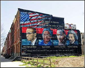 A painted mural shows the faces of Malcolm X, Ella Baker, Martin Luther King, and Frederick Douglass