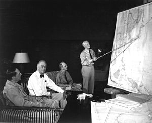 Three men are seated in lounge chairs. One is standing, holding a long stick and pointing to the location of Japan on a wall map of the Pacific.