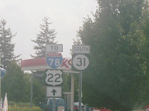 Two road signs adjacent to each other, with the left sign reading to Interstate 78 U.S. Route 22 with a black straight arrow on a white rectangle and the right sign containing a south banner and a black square with a white circle with the number 31.