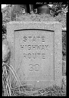 An old stamped bridge made and indented of stone off the side of the highway with the stamp reading State Highway Route 30
