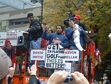 "Group of men on a raised platform. One holds a sign that reads ""JETER is playing GOLF today"" and ""THIS IS BETTER!""."
