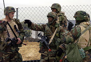 Picture of four soldiers outdoors in front of a fence; one soldier points to the left