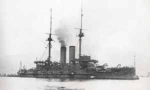 Large warship with smoke rising from the smokestack.