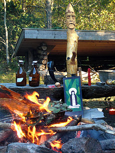 An outdoor fire burning in front of a wooden post with an anthropomorphic face carved into the top
