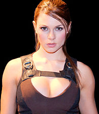 A close-up picture of a brunette woman dressed in a brown and black, sleeveless sports shirt.