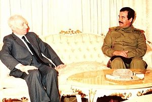 Saddam Hussein in uniform and man in suit, seated at opposite ends of a sofa and talking