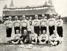 "Two rows of men: one row standing behind a second row seated on the ground. The men are wearing white baseball uniforms with ""Detroit"" across the chest and white baseball caps."