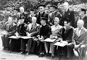 A group of men in uniforms, suits and academic dress sit for a formal group photograph