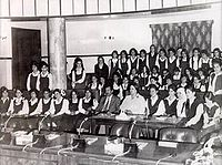 Black-and-white photo of Saddam Hussein, in a suit, with a group of women students