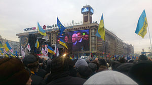 Dozens of blue and yellow Ukrainian flags are held aloft in a wide crowd watching large screens on a square building.