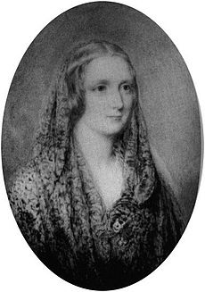 Black-and-white oval portrait of a woman wearing a shawl and a thin circlet around her head.