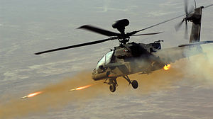 Colour photograph of an Apache Attack helicopter at right of image facing left, firing two rockets at a target beyond the bottom left of the frame.