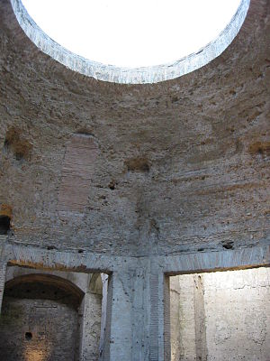 Bare concrete octagonal dome interior at Nero's palace showing flat sections springing from above square doorways and merging into a spherical shape that culminates in a large circular oculus at the top