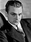 Black-and-white photo of James Cagney in 1930—a white man with serious features and an arched eyebrow, dark eyes and hair combed back, wearing a suit and around 30 years of age.