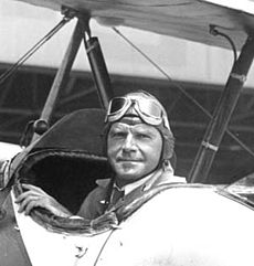 Photograph of Roderick Burnham seated in a biplane, looking backwards toward the camera, and wearing a period pilot's cap and goggles.