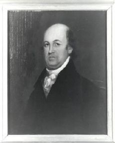 A bald man in a white shirt and tie and black jacket
