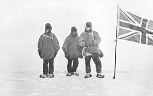 Three men in heavy clothing stand in line on an icy surface, next to a flagstaff from which flies the flag of the United Kingdom of Great Britain and Ireland